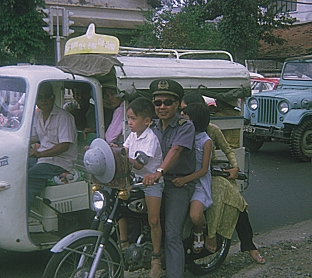 A man carrying his children on his scooter, in Saigon in 1970.